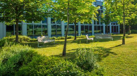 Außenbereich mit Sitzbänken und Bäumen